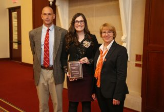 Kira Barclay with alumni award standing between Dean Schmittmann and Hal Schenck